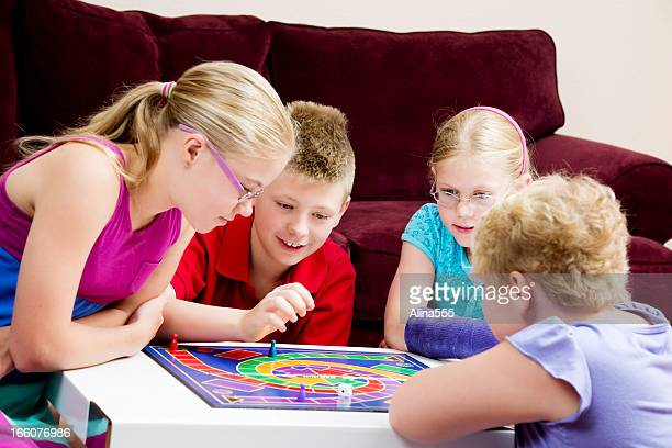 Gruppe der Kinder spielen Brettspiel in einem Wohnzimmer