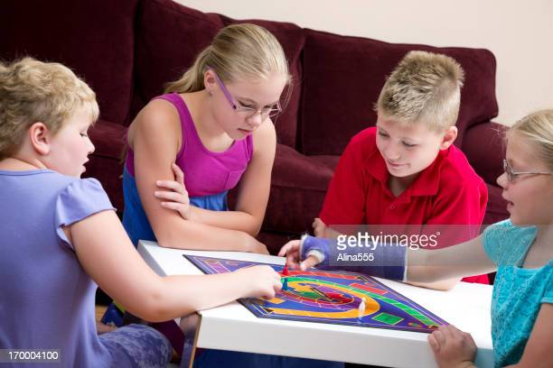 Group of kids playing board game in a living room