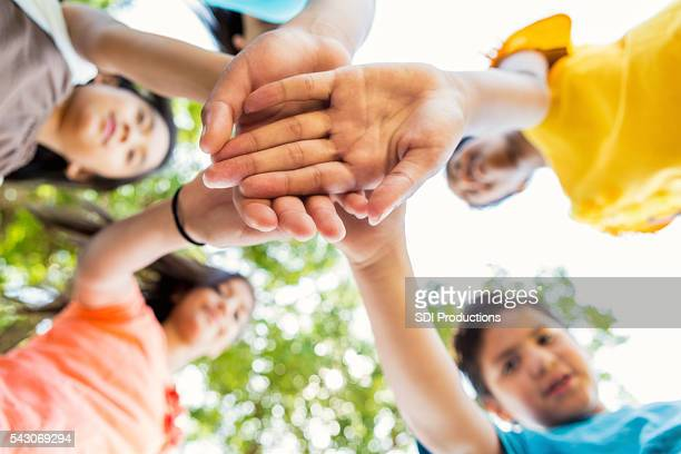 Group of kids put their hands together at park