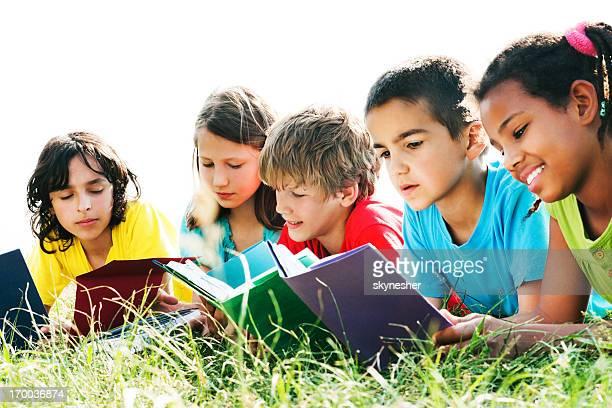 Grupo de niños leyendo libros en el campo.