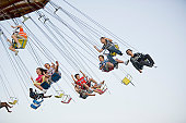 Group of kids riding the spinning swing at an amus