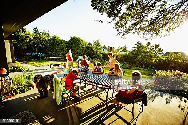 Group of kids sitting on patio on summer evening