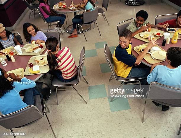 Group of kids (12-14) smiling in cafeteria, elevated view
