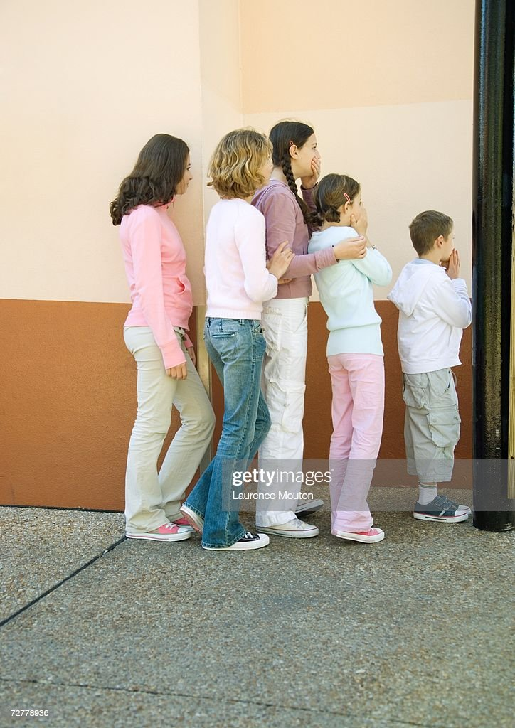 Group of kids standing in line, come covering mouths