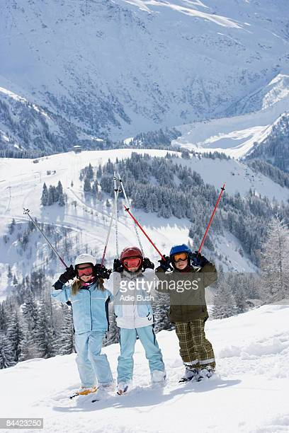 Group of kids standing in snow with skis