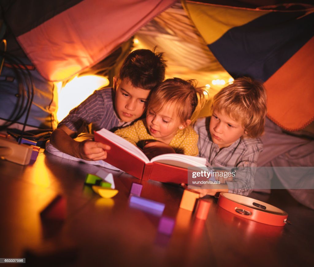 Group of kids under blanket fort reading a story together : Stock-Foto