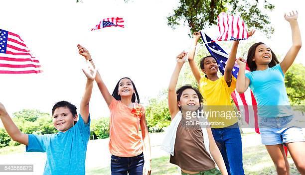 Gruppo di bambini onda bandiere americane Giorno dell'Indipendenza parata