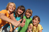 group of happy smiling kids with thumbs up