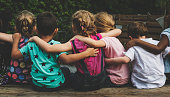 Group of kindergarten kids friends arm around sitting together