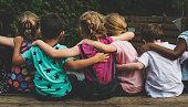Group of kindergarten kids friends arm around sitting together