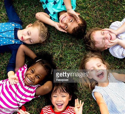 Group of kindergarten kids lying on the grass at park and relax with smiling : Stock Photo