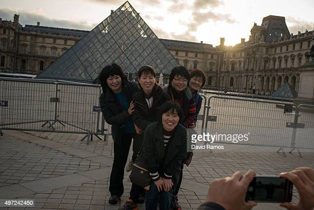 A group of Korean tourists pose for a picture outside the main entrance of the Louvre musem on November 15 2015 in Paris France As France observes...