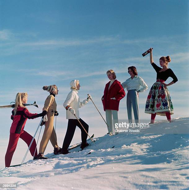 A group of ladies welcome their friends back from a day's skiing with an apres ski drink
