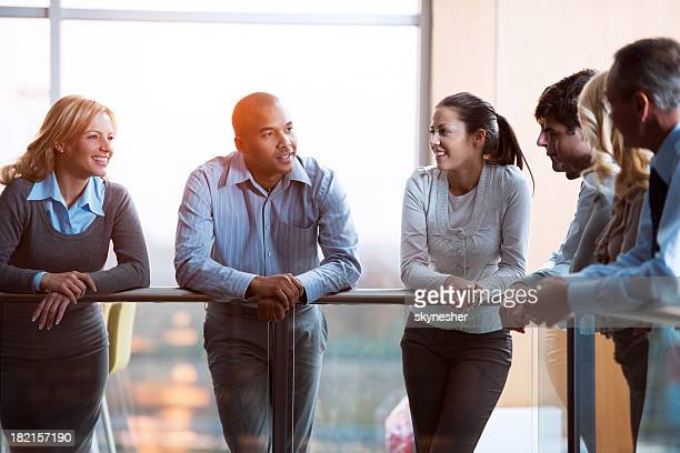 Group of laughing  businesspeople talking in a lobby