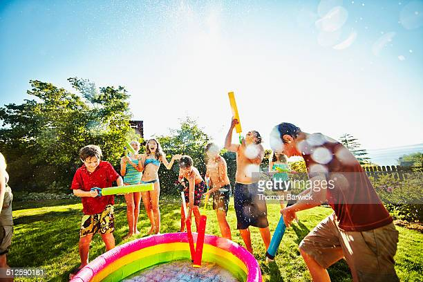 Group of laughing kids filling up squirt guns