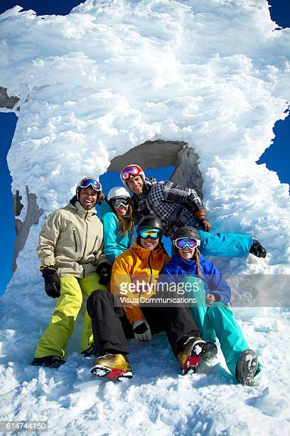 Group of laughing skiers and snowboarders posing for photo.