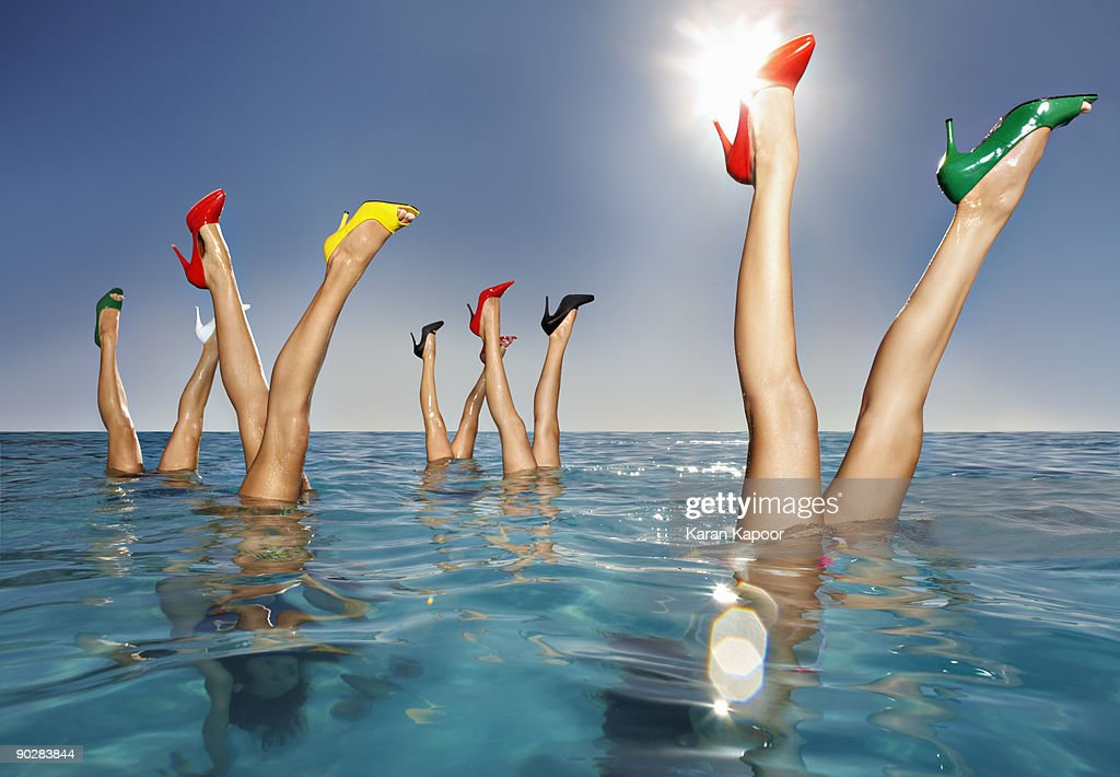 Group of legs portruding out of infinity pool : Stock Photo