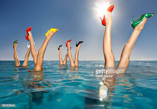 Group of legs portruding out of infinity pool