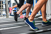 Group of legs wearing sneakers running on treadmill  at sport gym.