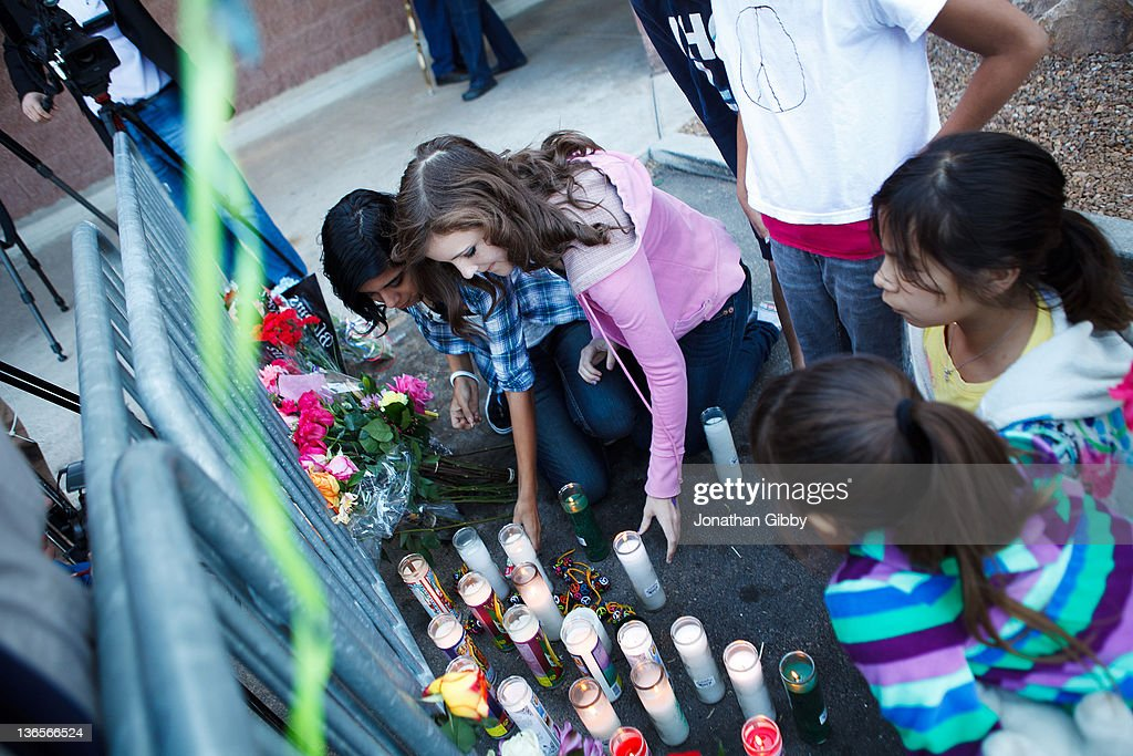 A group of local children place flowers at a memorial for the six people that lost their lives in a deadly shooting last year in the parking lot of the La Toscana Village Safeway January 8, 2012 in Tucson, Arizona. Memorial services will be held throughout the day in Tucson to commemorate the one year anniversary of a shooting rampage that killed six people and wounded more than a dozen more including U.S. Rep. Gabrielle Giffords (D-AZ).