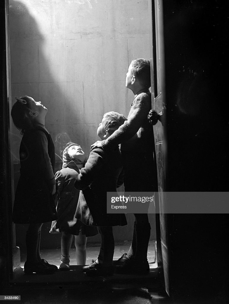 A group of London children inspecting bomb damage outside their front door.