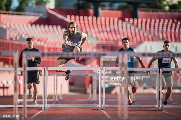 Group of male athletes jumping hurdles on a race.