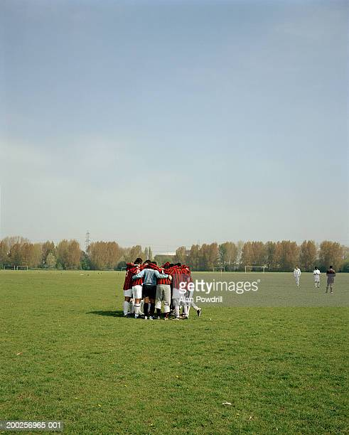 Group of male football players in huddle