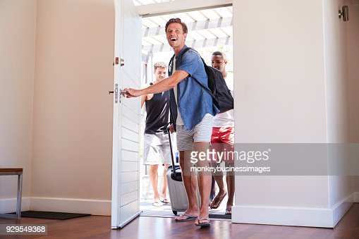 Group Of Male Friends Arriving At Summer Vacation Rental : Stock Photo
