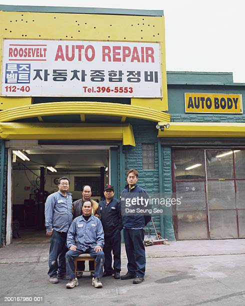 Group of male workers in front of auto repair shop, portrait