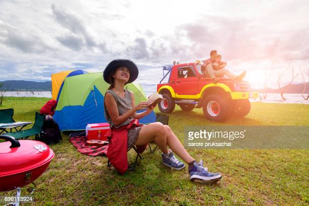group of man and woman enjoy traveling with convertible off road car, sky cleared in background . Holiday , vacation , summer concept .