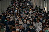 Group of many salary man wearing face mask for protect micro dust in air while going to their workplace during pm2.5 air pollution crisis in Bangkok at moring rush hour.