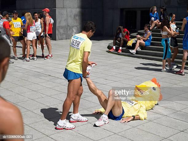 Group of marathon runners stretching on sidewalk, one wearing chicken head