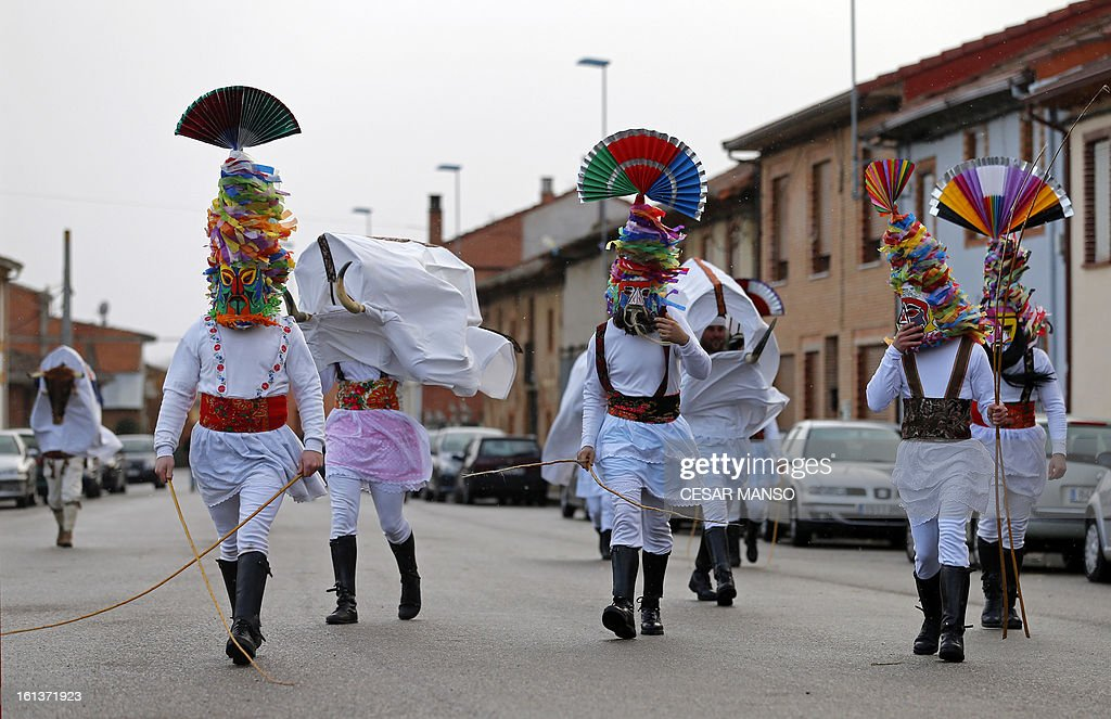 A group of masked men 'Antruejos' parade carrying cowbells tied to their backs during the carnival of Velilla de la Reina, in the northern Spanish province of Leon, on February 10, 2013. AFP PHOTO / CESAR MANSO