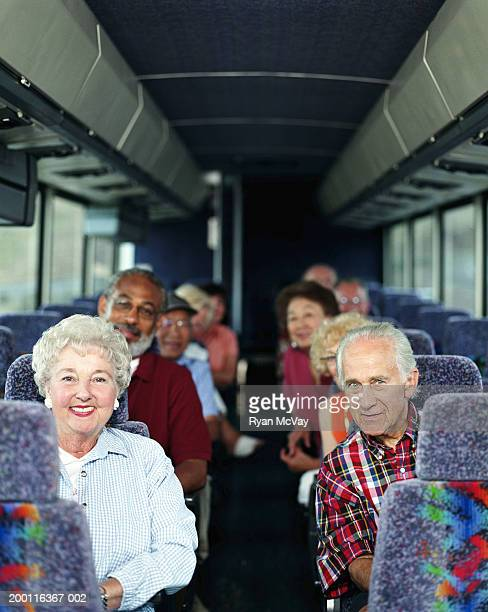 Group of mature adults on coach bus, smiling