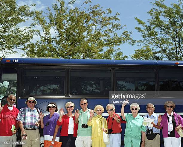 Group of mature adults standing beside charter bus, smiling, portrait