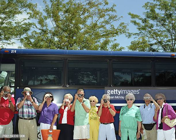 Group of mature adults standing beside charter bus, taking photographs