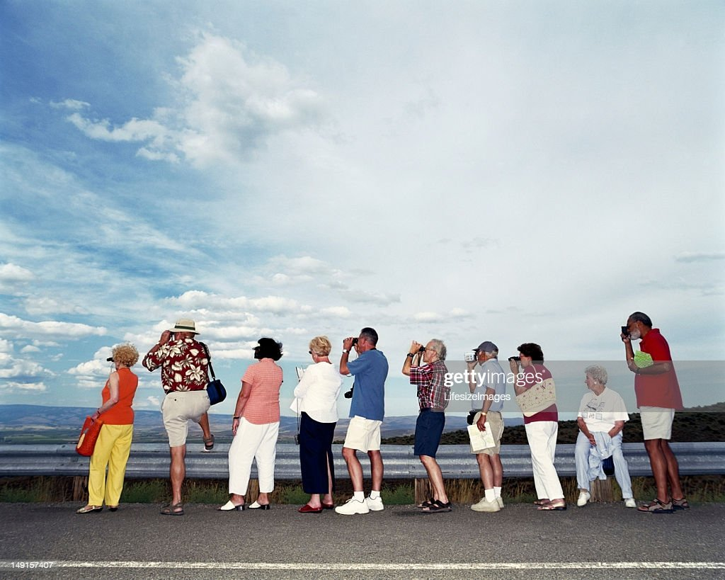 Group of mature adults using binoculars and cameras : Stock Photo