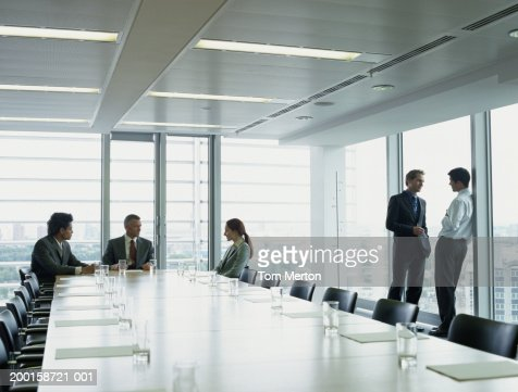 Group of mature and young business colleagues talking in boardroom