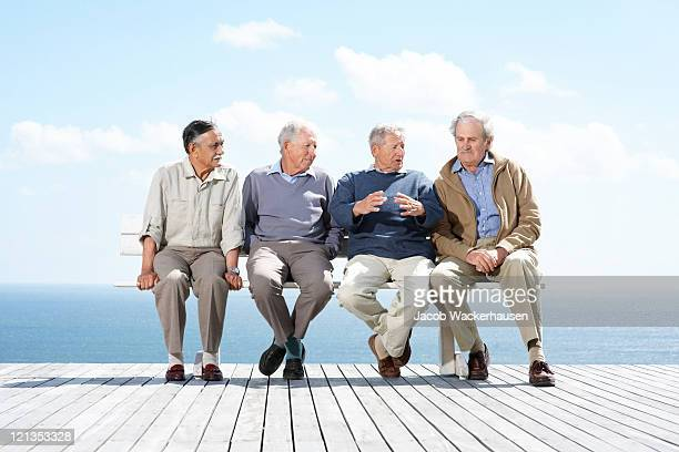 Group of mature male friends sitting together on bench