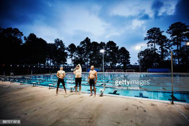 Group of mature men stretching on deck of outdoor pool before early morning workout