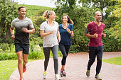 Healthy group of people jogging on track in park. Happy couple enjoying friend time at jogging park while running. Mature friends running together outdoor.