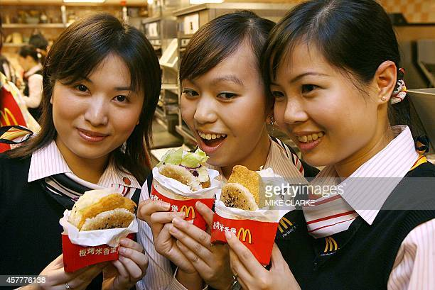 A group of McDonald employees pose with food products at a restaurant in Hong Kong 06 June 2006 Mcdonald's was established in 1955 and now has 30000...