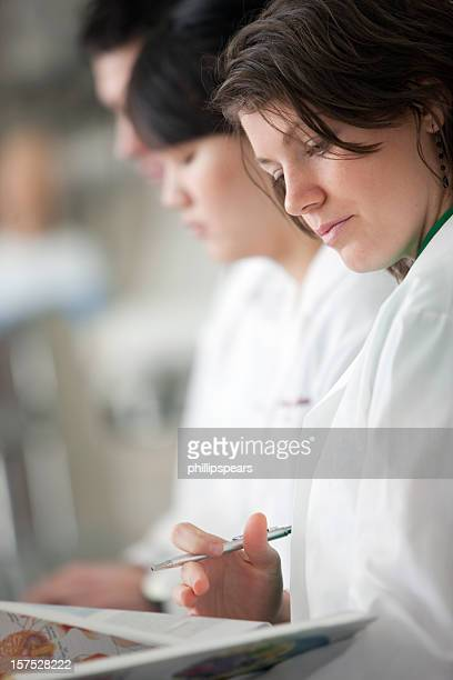 Group of medical professionals writing on clipboards