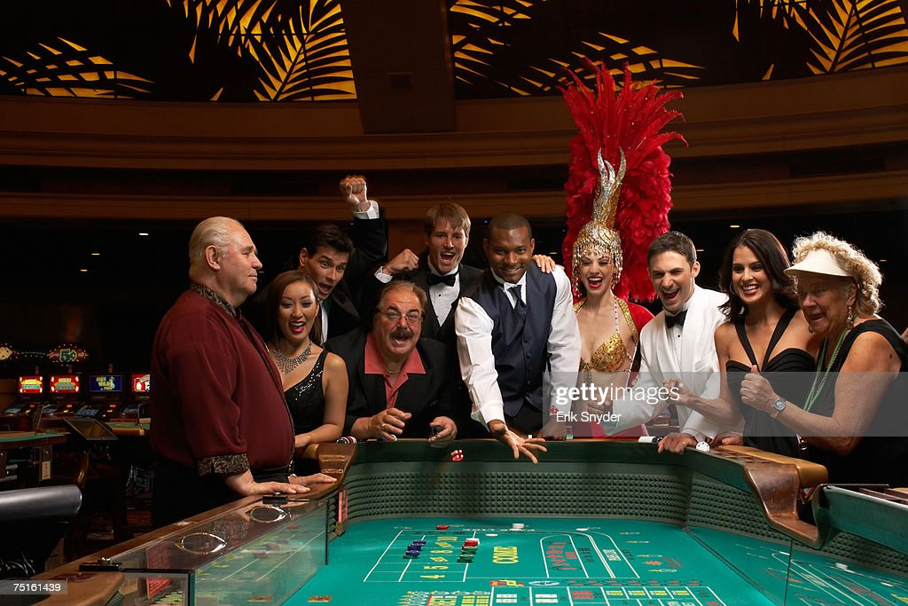 Group of men and women, casino worker and dancer playing roulette, man throwing dices