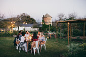 Group of men and women having outdoors party in restaurant. friends sitting around a table and having dinner.
