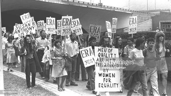 A group of men and women march together holding signs while participating in an ERA protest in Pittsburgh PA 1976