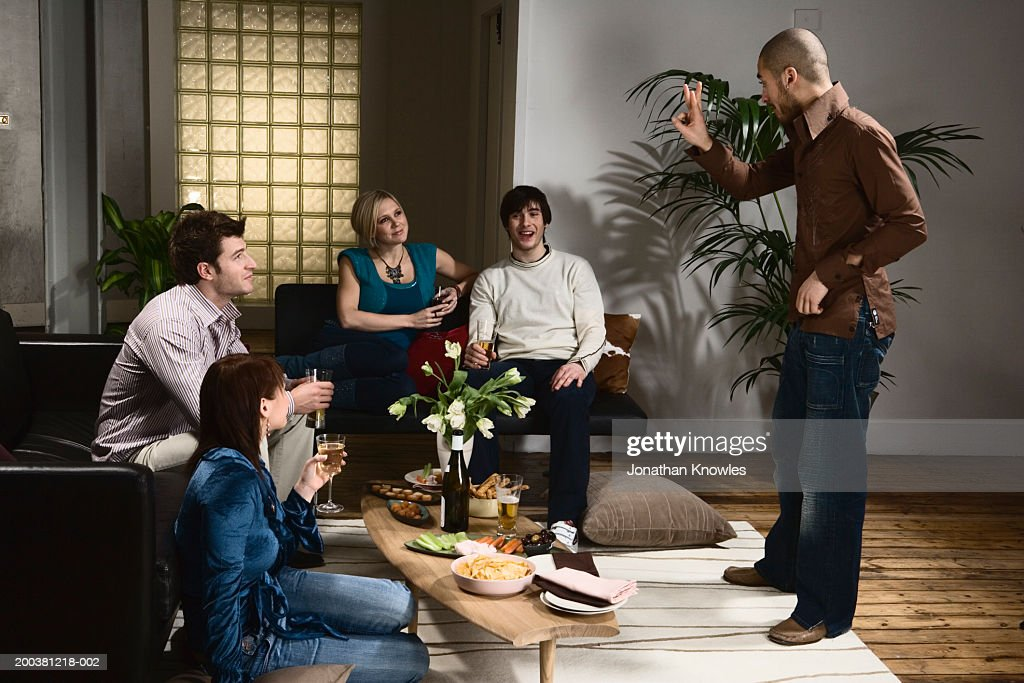 Group of men and women playing charades in lounge, man miming : Stock Photo