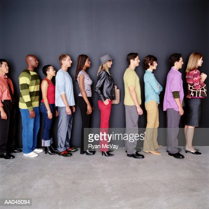 Group of men and women waiting in line, side view