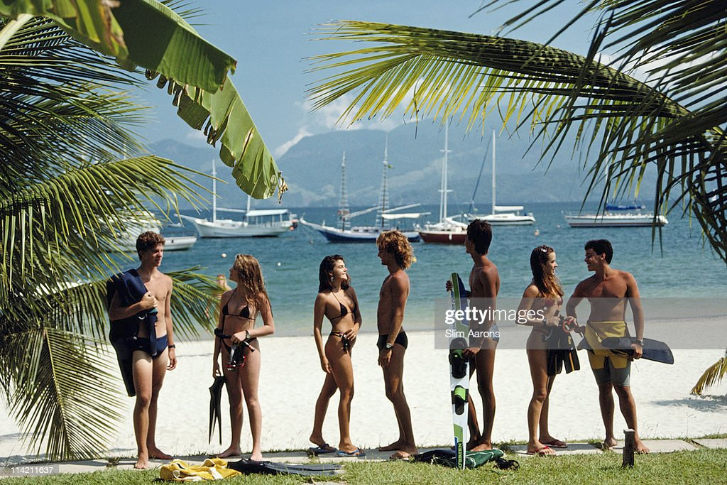 A group of men and women wearing beachwear on Portogallo beach in Brazil, in January 1988. Beyond the beach, a number of boats and yachts are on the waters off the coast.