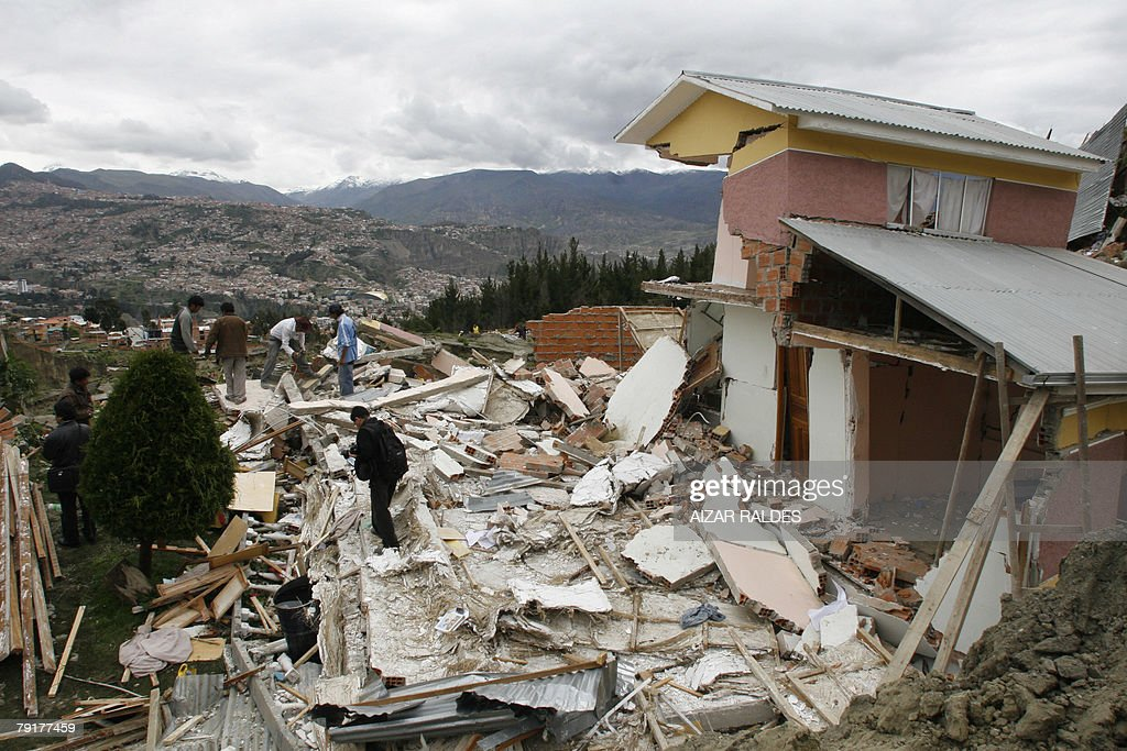A group of men attempt to recover part of their belongings from the rubble 23 January, 2008 in Alpacoma valley in La Paz, after heavy rains caused a landslide that devastated 11 houses. The Bolivian government decreed on Tuesday a national emergency to counteract damages caused by heavy rains and floods battering the country since last November. According to official sources, 22 people died so far and about 20,000 families have been damaged.